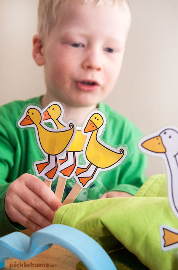 child playing with duck puppets