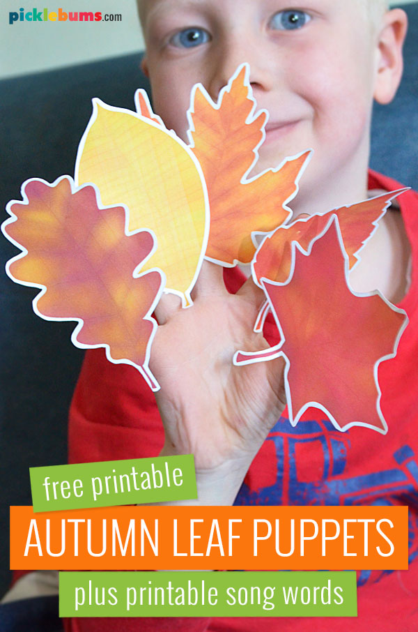 child holding paper autumn leaf puppets