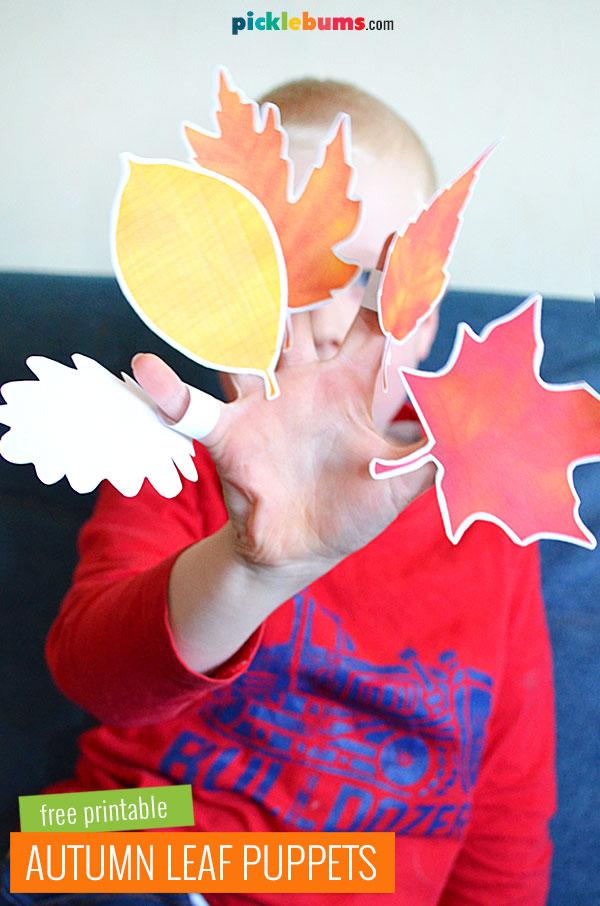 Boy holding paper autumn leaf puppets