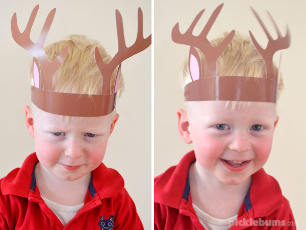 toddler wearing reindeer antler hat and making faces