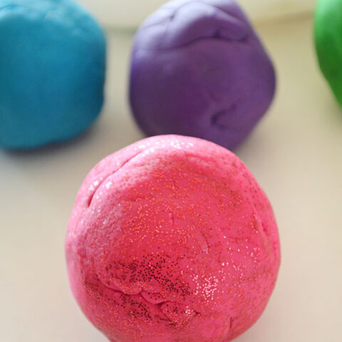 pink playdough with more dough behind it